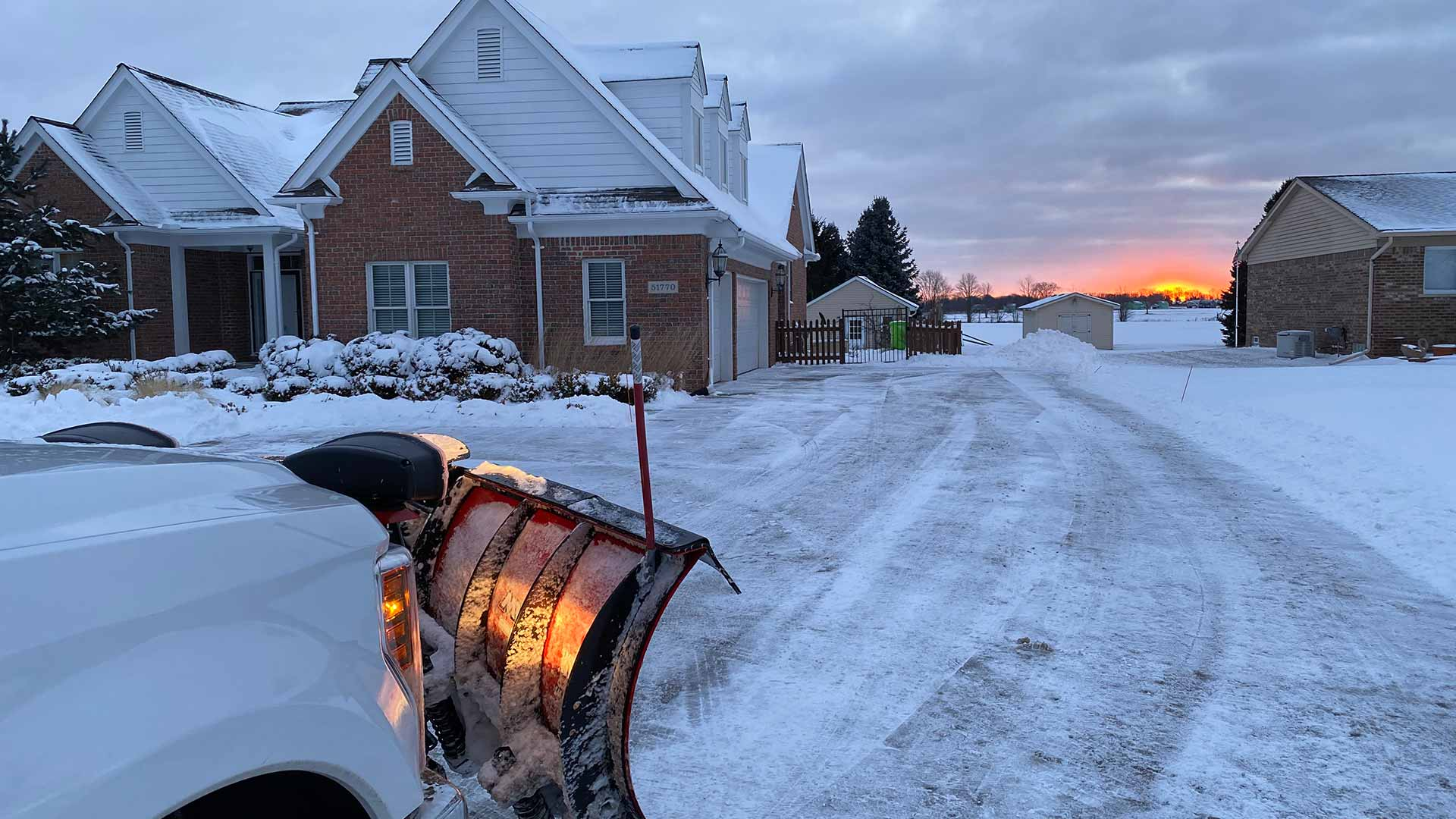 Truck with snow plow clearing snow at a Macomb, MI home at sunrise.