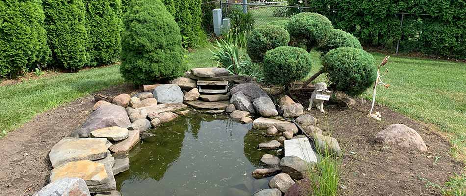 A water feature landscape after spring yard cleanup services in Macomb, MI.